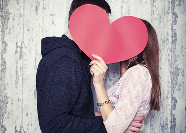 A couple kiss behind a paper heart