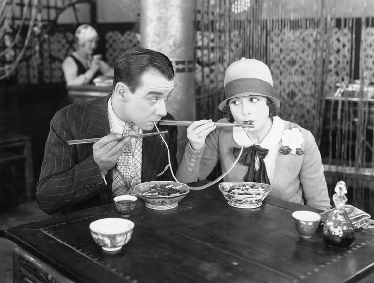 Vintage couple at a restaurant sharing a spaghetti string