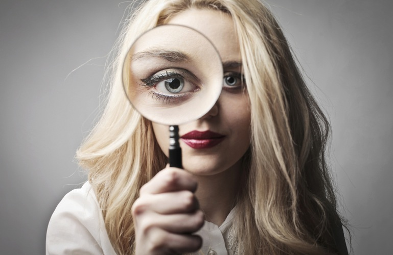 A woman looks through a magnifying glass