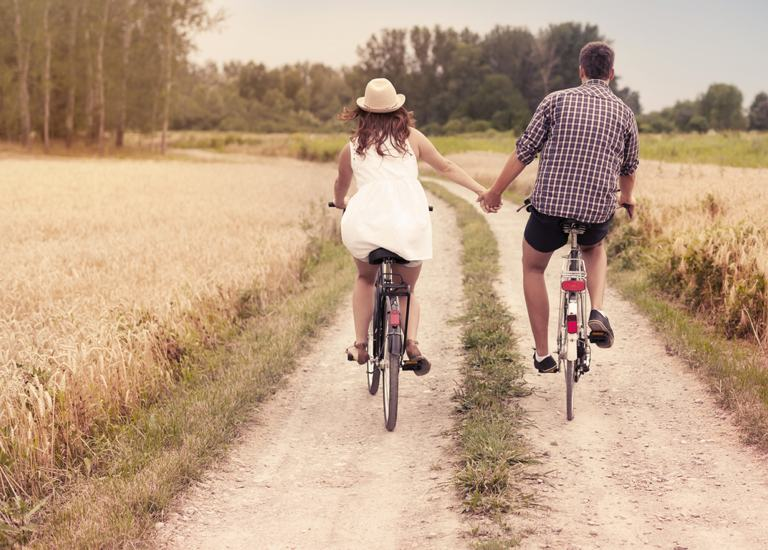 Cycling couple holding hands