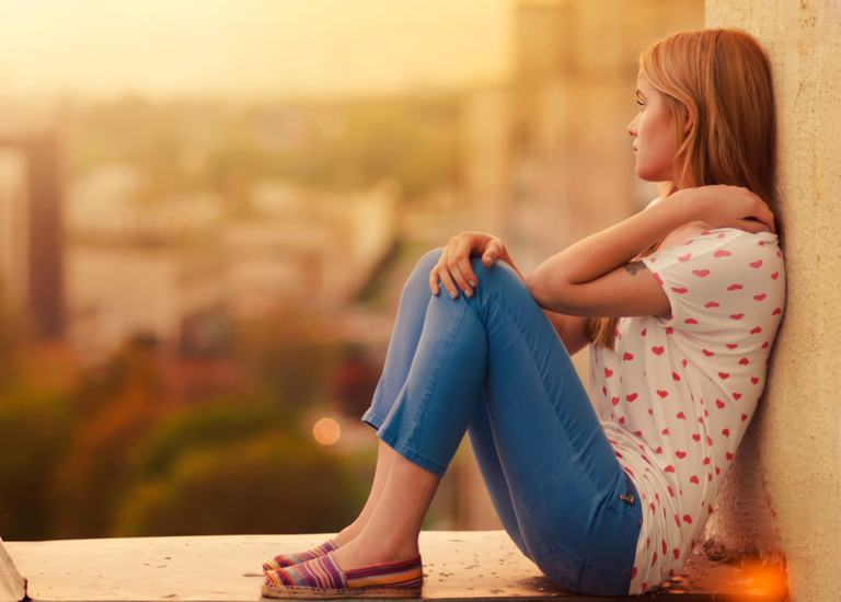 Girl sitting against a wall