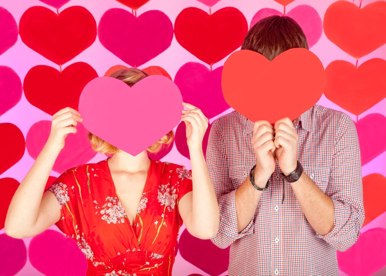 Couple with hearts covering face
