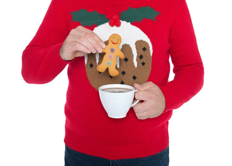 Man in Christmas jumper with tea