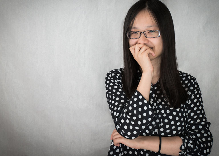 Nervous young woman holding her hand to her mouth