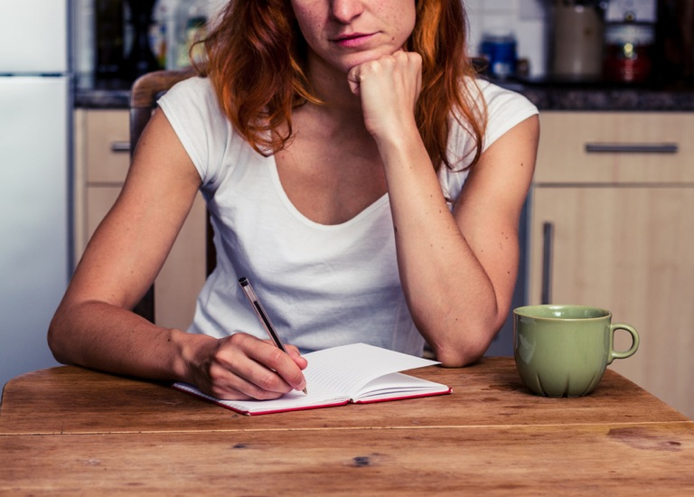 Woman sitting in her kitchen writing