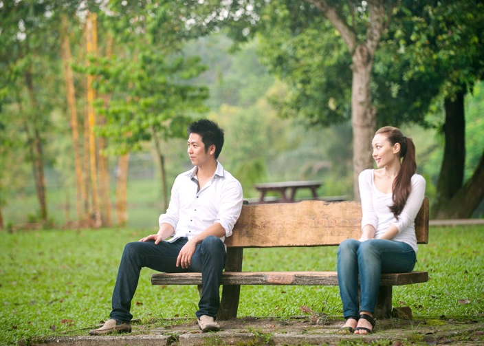 Asian couple sitting on a park bench