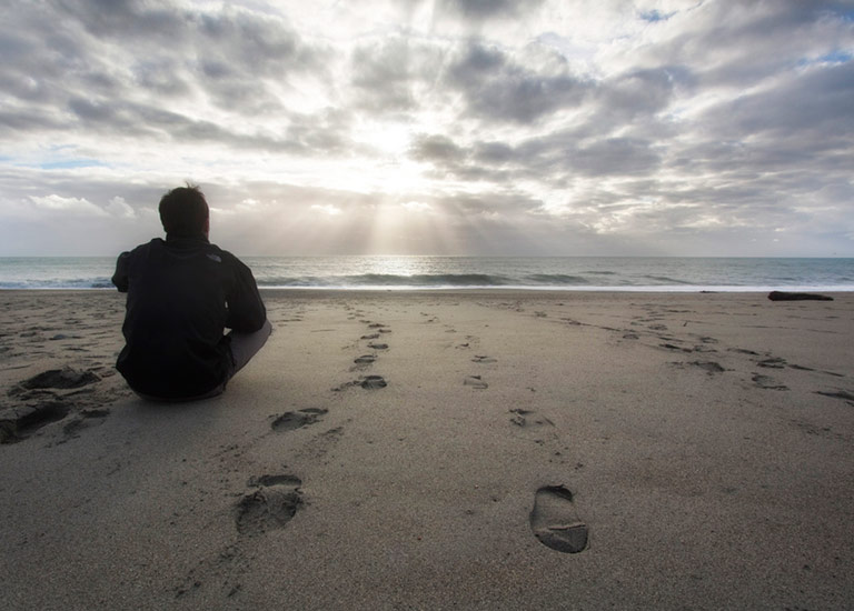 Man sitting reflectively on the beach