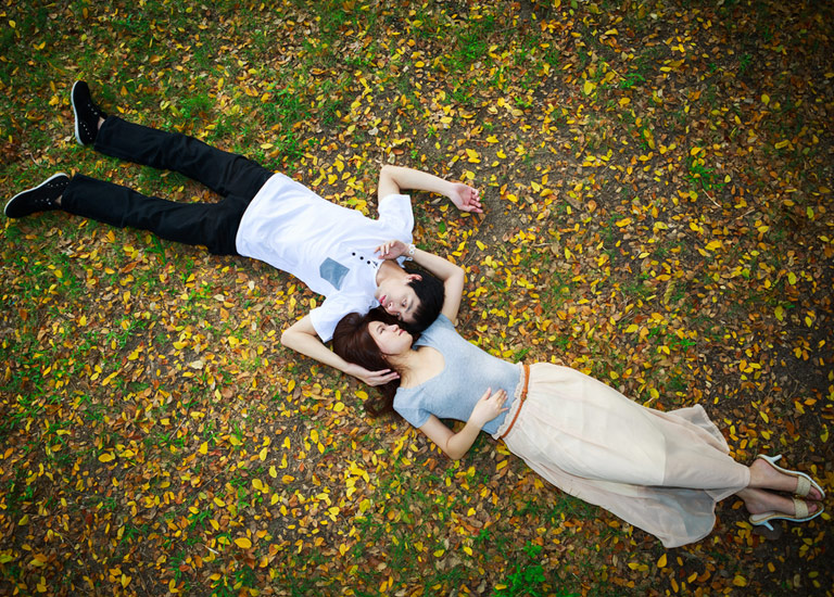 Young couple lying on leaves