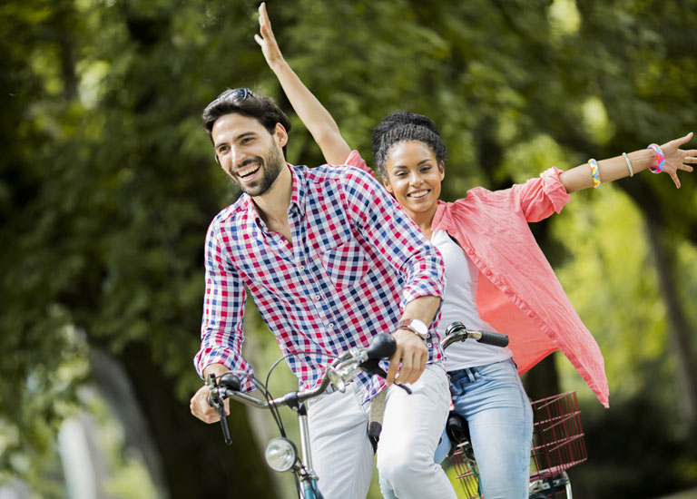 A young couple riding a tandem bicycle