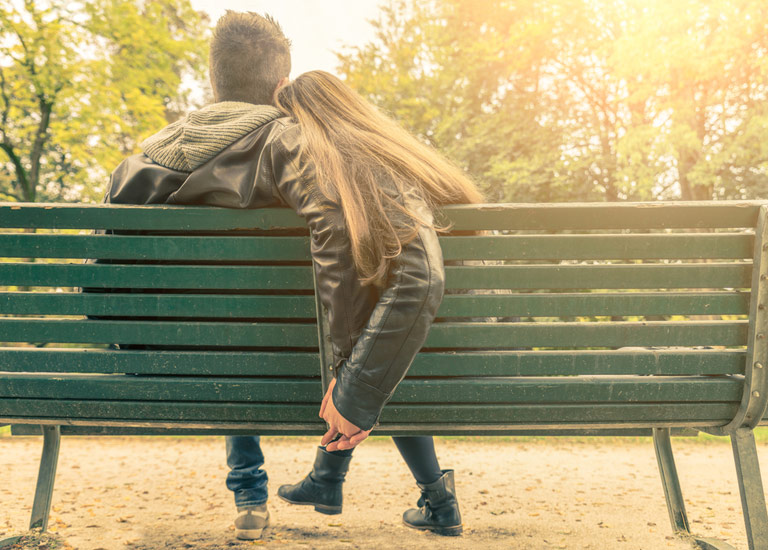A couple sitting together on a bench