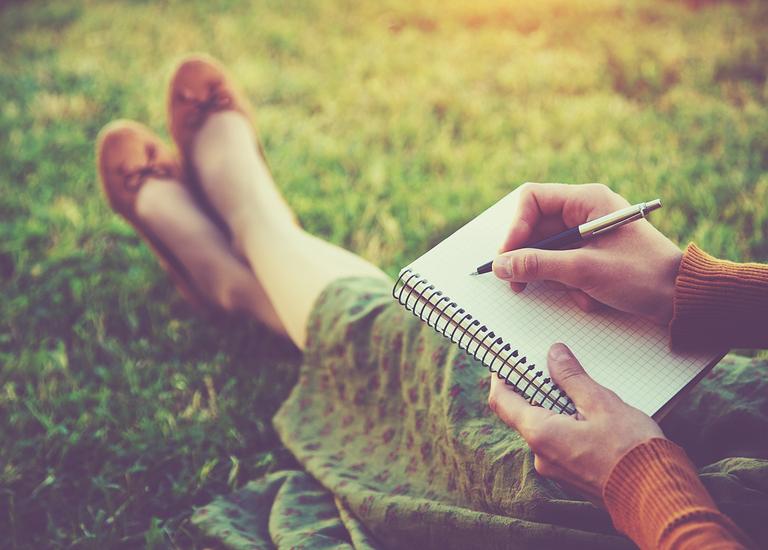 girl sitting writing letter