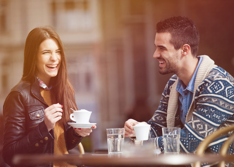 A man and woman laughing whilst at a cafe
