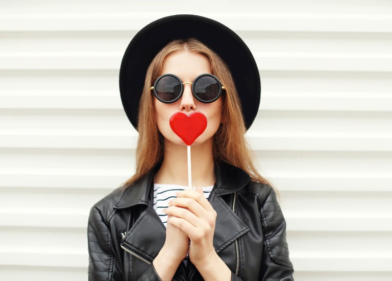 Woman holding heart-shaped lollipop