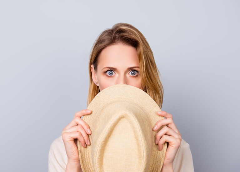 Woman hiding behind a hat