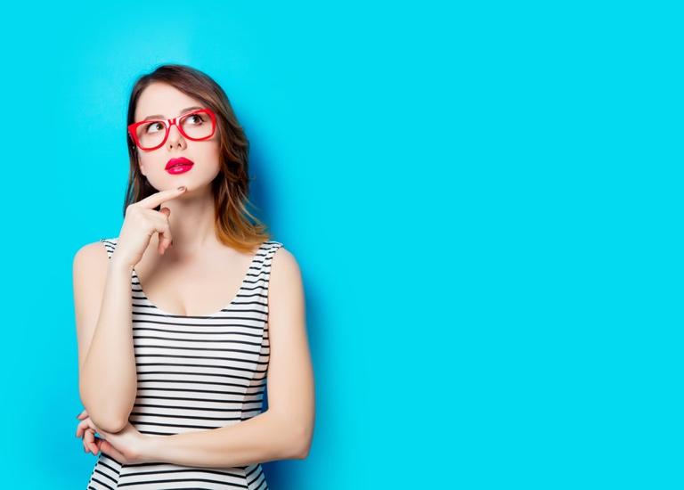Woman on plain blue background thinking