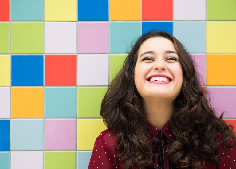 Smiling woman in front of colourful tiles