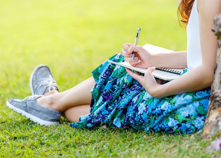 Woman writing in a notepad whilst leaning on a tree