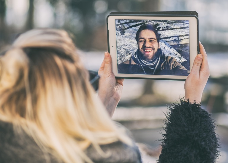 A couple video chatting on a tablet
