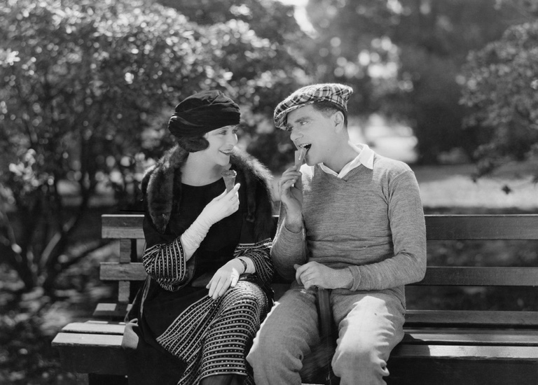 Black and white photo of a vintage couple sitting on bench