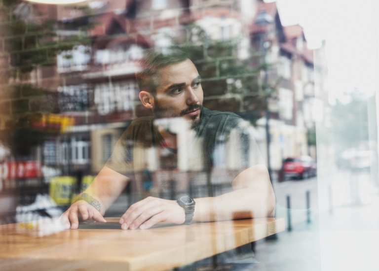 A man looking out of a cafe window