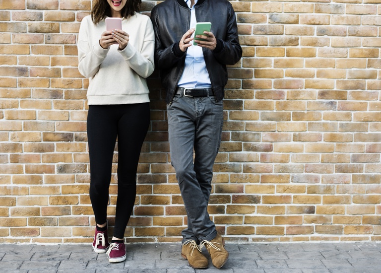 Two people messaging on their smartphones