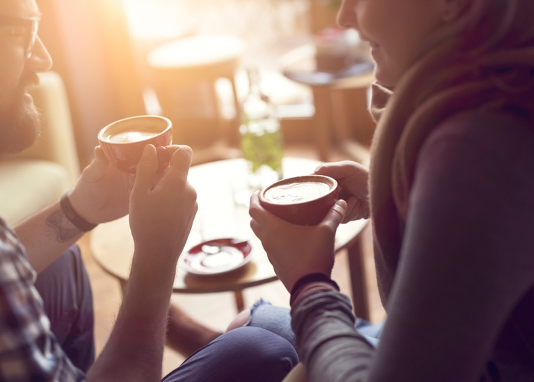 Two people share a coffee and a chat