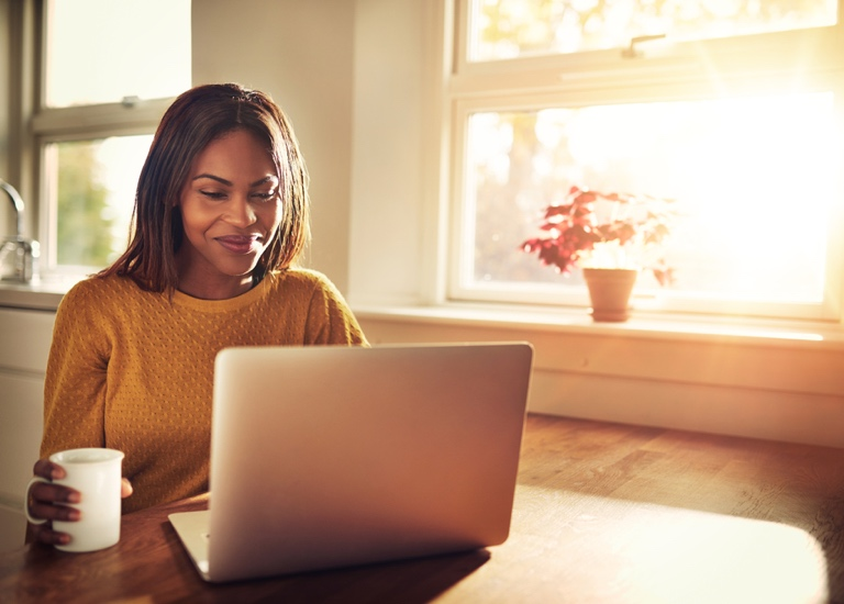 A happy woman sitting at a table working on a laptop