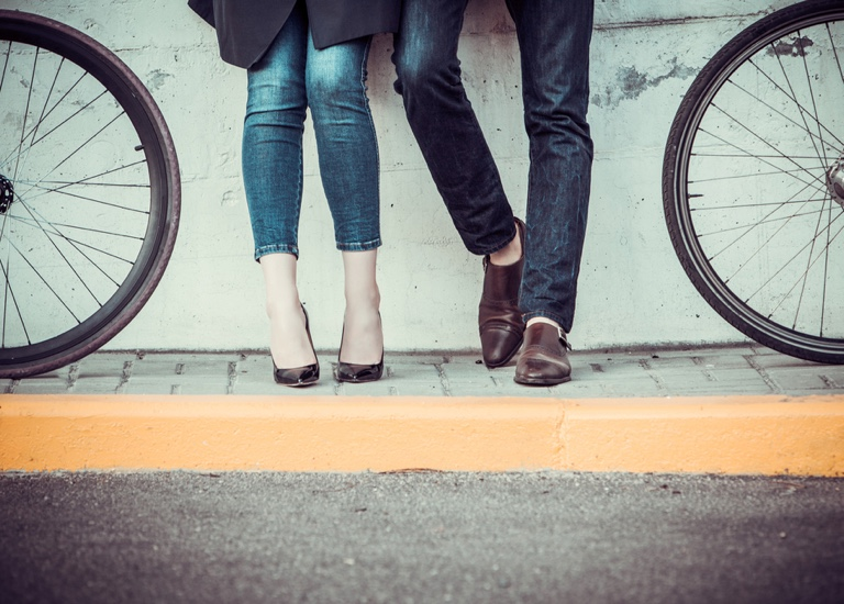 A young couple standing by a wall next to bicycles