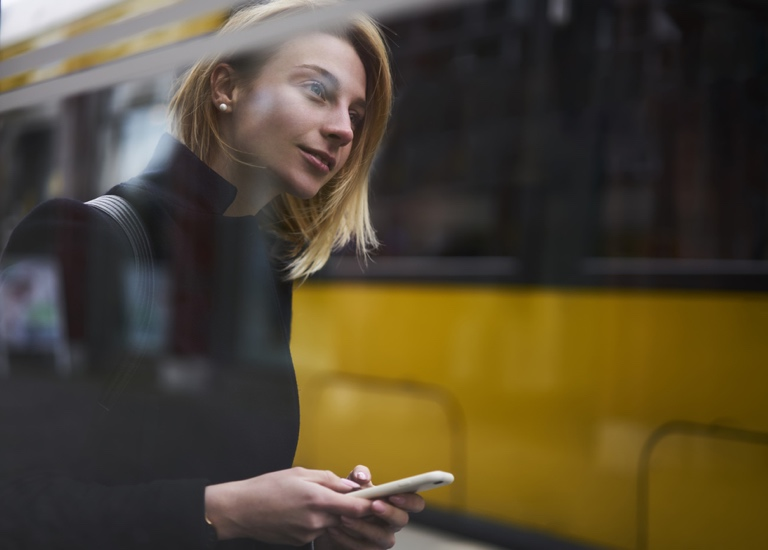 A young women checks her phone whilst walking down the street