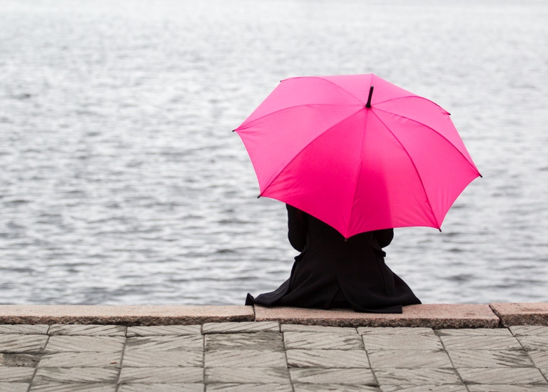 Woman holding umbrella looking out across the water