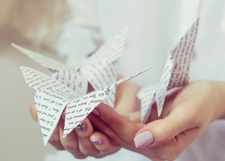 Close up of a woman holding an origami butterfly