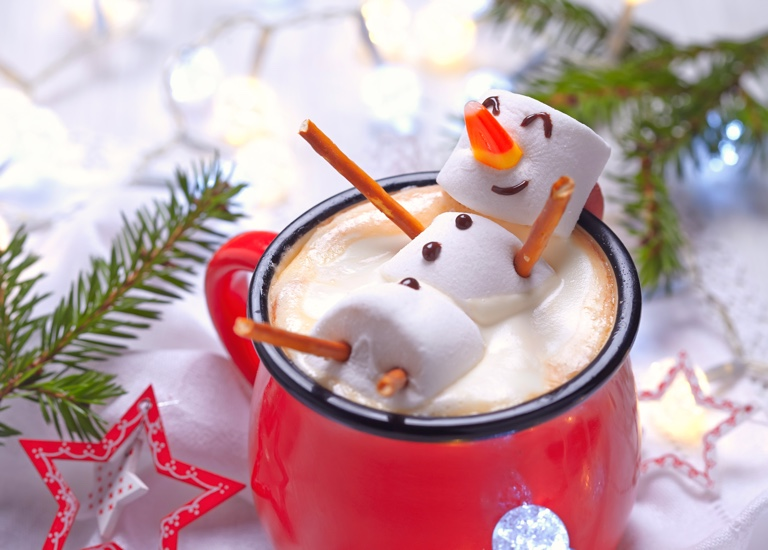 A happy marshmallow snowman in a mug of hot chocolate
