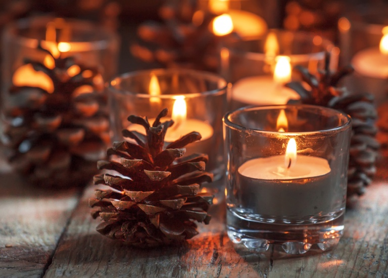 Tranquil, festive picture of a candle and a pine cone