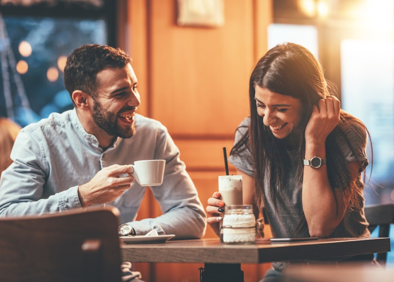 A man and a woman drinking coffee and laughing together