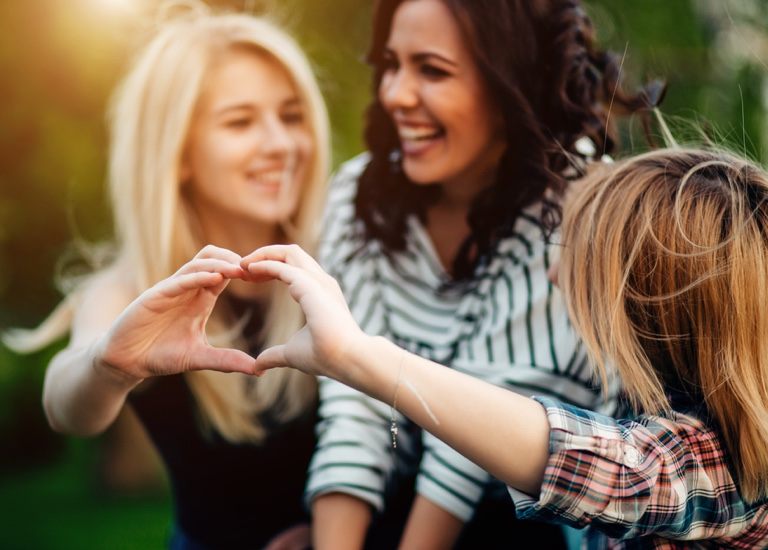 Friends laughing and making heart gesture