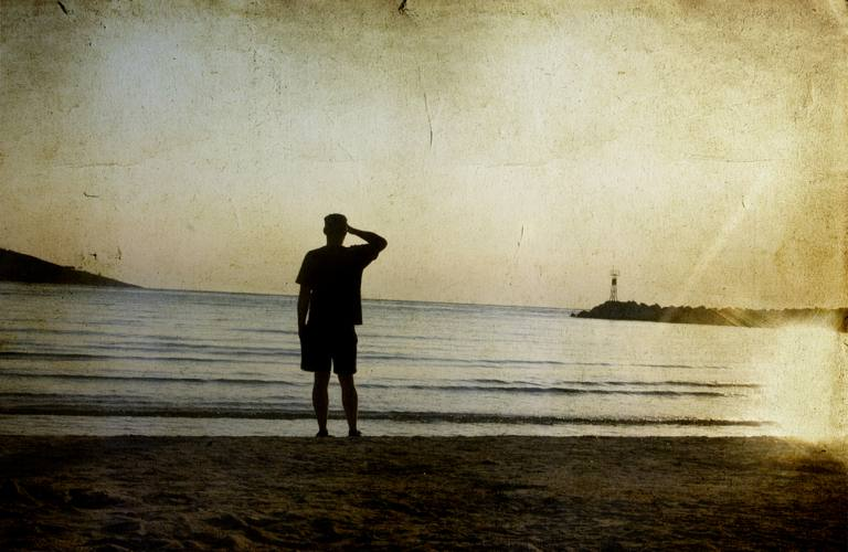 Man on beach watching a sunset