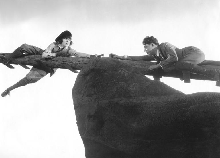 A man and woman hang precariously on a pole