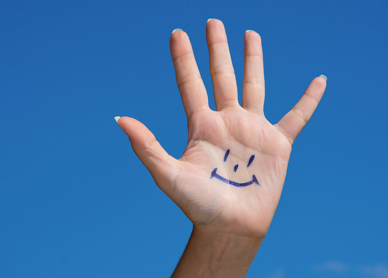 Hand showing a smiley face and five fingers