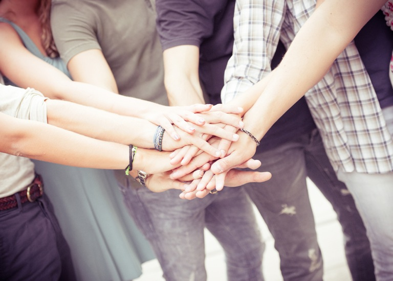 group of friends piling up hands in unity