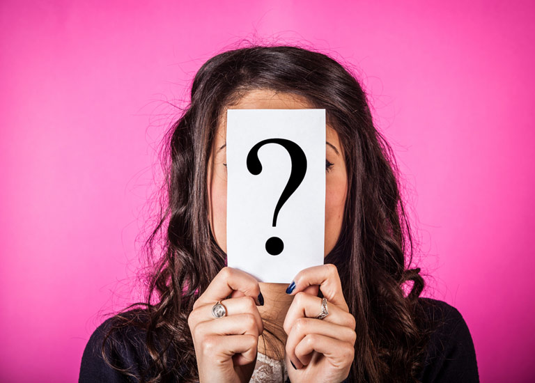 Woman holding up a question mark