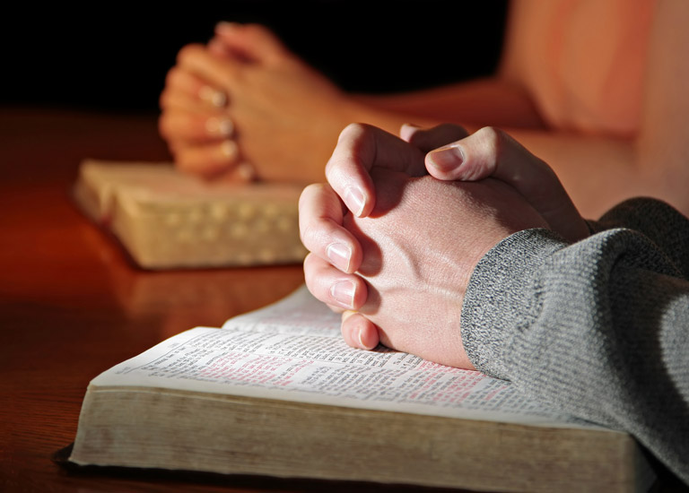 A couple with hands in prayer over The Bible