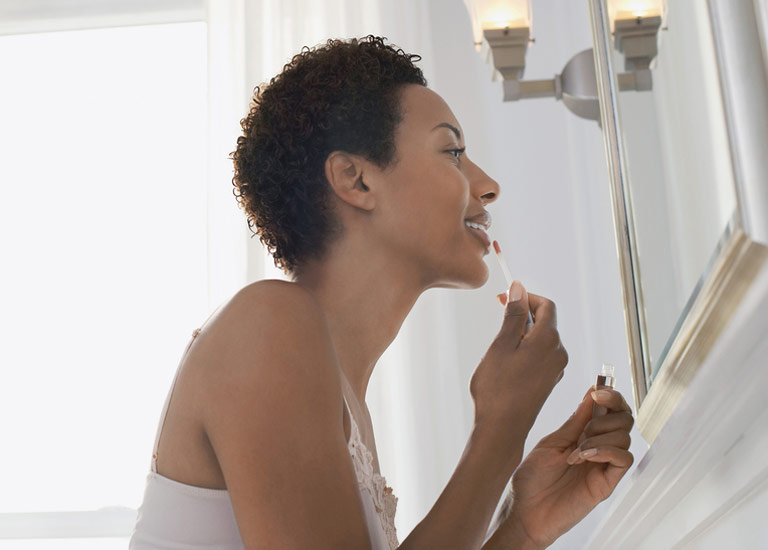 Woman looking in the mirror applying lipstick