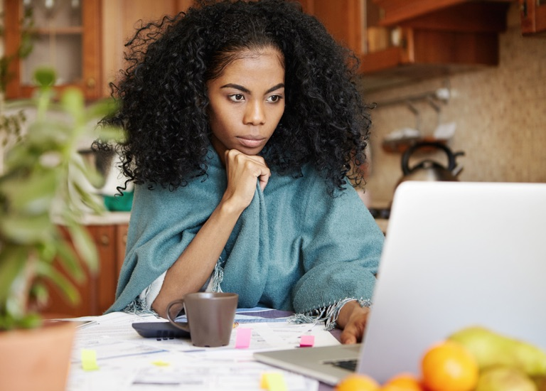 A woman looking inquisitively at a laptop