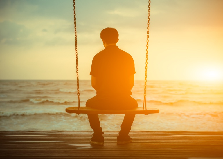 Man sitting on a swing alone