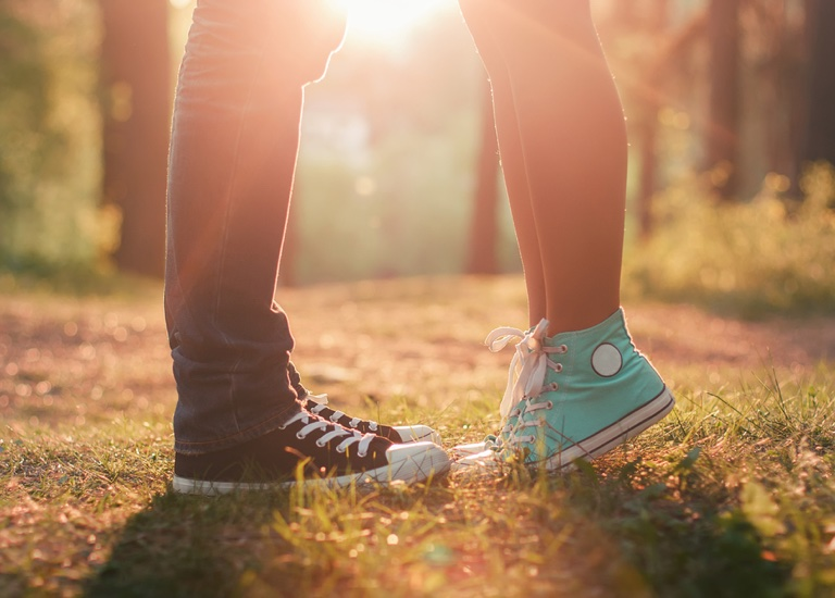 Young couple kissing whilst standing in sunlight