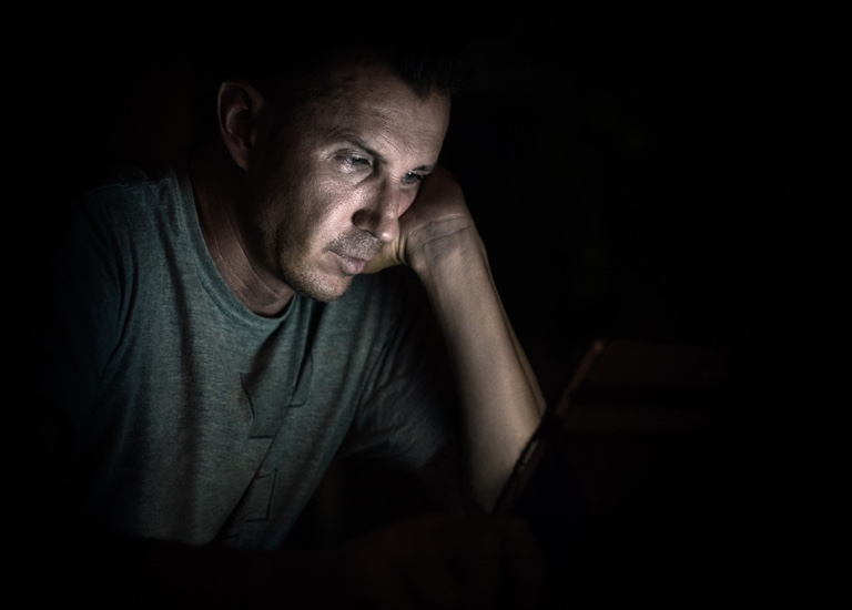 Man looking at a laptop in the dark