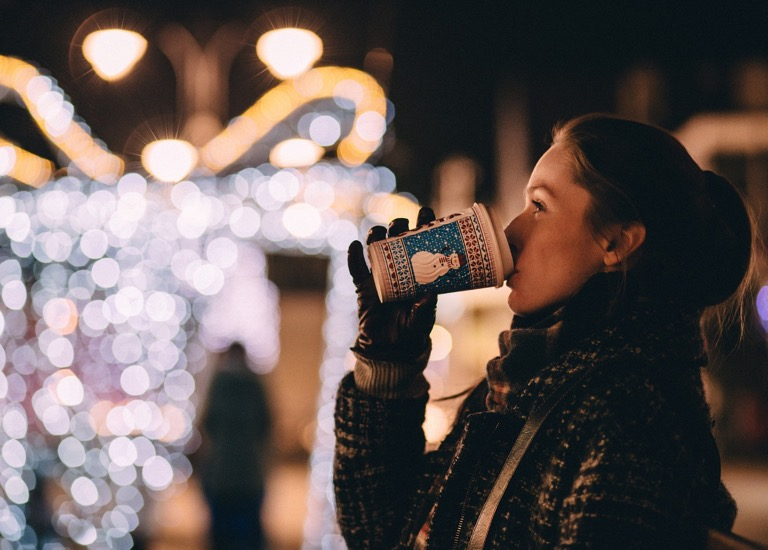 Woman drinking a hot drink with a Christmas theme