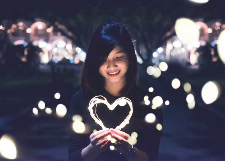 Woman looking at a heart shaped light