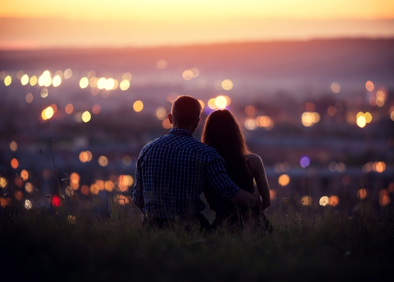 A couple overlooking a city at sunset