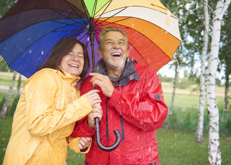 Smiling couple holding an umbrella